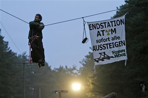A Robin wood activist hangs on a rope crossing a road close to the nuclear interim storage facility in Gorleben, Germany, Tuesday, Nov. 9, 2010. A shipment of nuclear waste from France made it to a storage facility in northwestern Germany on Tuesday, after police worked through the night to clear a road blockade by more-than 3,000 protesters. Banner reads 'Final Stop, Atom, all get off immediately'. (AP Photo/Ferdinand Ostrop)