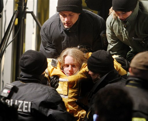 A member of environmental organization Greenpeace is carried out of a truck in which she was fixed in a concrete block for more than eleven hours in Dannenberg, northern Germany, early Tuesday, Nov. 9, 2010. The truck with a special box construction inside and under the truck blocked the first cross road where a transport of nuclear way is supposed to pass for more than eleven hours. The castor train with nuclear waste is underway from French La Hague to the nuclear interim storage plant in Gorleben. (AP Photo/Michael Probst)