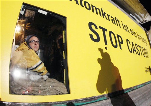 A member of environmental organization Greenpeace looks out of a window on which he is fixed in a van in Dannenberg, northern Germany, Monday, Nov. 8, 2010. The van with its special box construction blocks the first cross road where a transport of nuclear way is supposed to pass soon. The inside box was put down on the street so that the van cannot be moved. The castor train with nuclear waste was underway from French La Hague with delay due to various protests of anti nuclear activists. (AP Photo/Michael Probst)