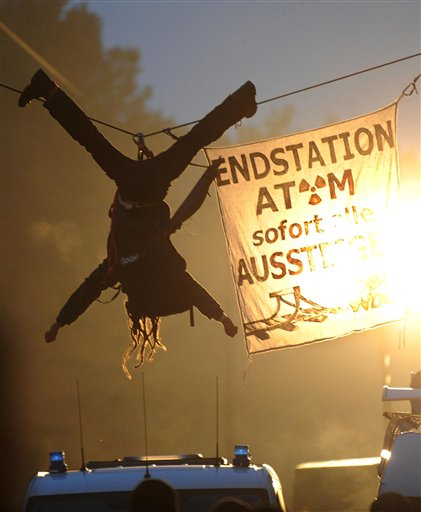 An activist of the environmental organization Robin Wood hangs from a rope that was fixed between two trees during a protest against the nuclear waste transport in Gorleben, northern Germany Tuesday Nov. 9, 2010. Trucks carrying 123 tons of nuclear waste have finally reached the storage facility in Gorleben after police worked through the night to clear thousands of protesters blockading the roads. Banner reads 'Final Stop, Atom, all get off immediately'. (AP Photo/dapd, Thomas Lohnes)
