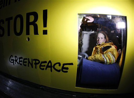 A member of environmental organization Greenpeace looks out of a truck in which she fixed herself for more than eleven hours in a concrete block in Dannenberg, northern Germany, Monday, Nov. 8, 2010. The truck blocks the first crossroad where a transport of nuclear way is supposed to pass. The shipment reached a railway depot in Dannenberg on Monday, where workers spent the day transferring containers of nuclear waste from the rails to trucks that are to carry it on the last leg of its journey to the site in Gorleben, 20 kilometers (12 miles) away. (AP Photo/Michael Probst)