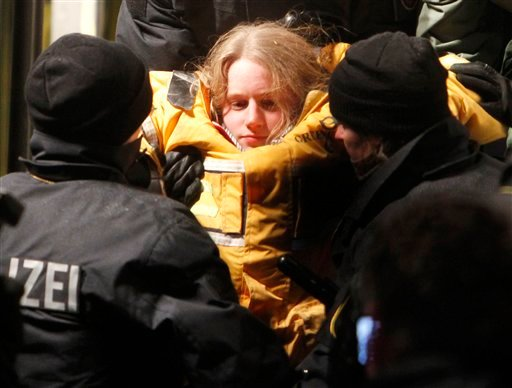 A member of environmental organization Greenpeace is carried out of a truck by police officers in which she fixed herself in a concrete block for more than eleven hours in Dannenberg, northern Germany, early Tuesday, Nov. 9, 2010. The truck with a special boxes set inside and under that blocked the first crossroad where the transport of nuclear way is supposed to pass for more than eleven hours. The shipment reached a railway depot in Dannenberg on Monday, where workers spent the day transferring containers of nuclear waste from the rails to trucks that are to carry it on the last leg of its journey to the site in Gorleben, 20 kilometers (12 miles) away. (AP Photo/Michael Probst)