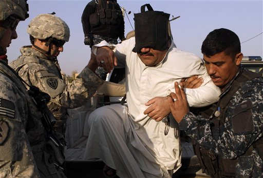 U.S. Army soldiers from 1st Battalion, 14th Infantry Regiment, left, and an Iraqi policeman, right, help a suspected terrorist step down from a truck during a joint operation in al-Shaheed village in Kirkuk province, north of Baghdad, Iraq, Wednesday, Nov. 10, 2010. The man was detained during a sweep by Iraqi police and Iraqi Army soldiers of several villages thought to be insurgent havens. U.S. troops were on hand to advise and assist if necessary. (AP Photo/Maya Alleruzzo)
