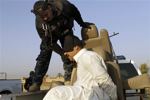 An Iraqi policeman adjusts the blindfold on a suspected terrorist during a joint operation in al-Shaheed village in Kirkuk province, north of Baghdad, Iraq, Wednesday, Nov. 10, 2010. The man was detained during a sweep by Iraqi police and Iraqi Army soldiers of several villages thought to be insurgent havens. U.S. troops were on hand to advise and assist if necessary. (AP Photo/Maya Alleruzzo)