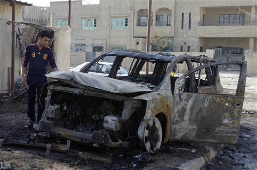 An Iraqi man inspects his destroyed car at the scene of a bomb attack in Baghdad, Iraq, Wednesday, Nov. 10, 2010. A string of bombings targeted Christian houses in Baghdad early Wednesday, killing and wounding several people, police said. (AP Photo/Khalid Mohammed)