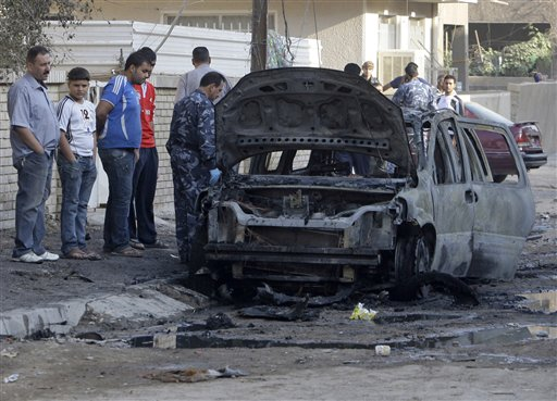 People gather at the scene of a bomb attack in Baghdad, Iraq, Wednesday, Nov. 10, 2010. A string of bombings targeted Christian houses in Baghdad early Wednesday, killing and wounding several people, police said. (AP Photo/Khalid Mohammed)