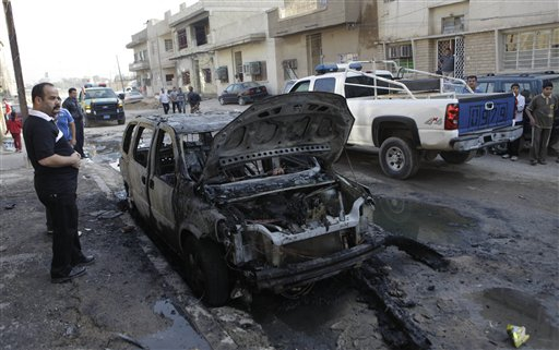Security forces and people gather at the scene of a bomb attack in Baghdad, Iraq, Wednesday, Nov. 10, 2010. A string of bombings targeted Christian houses in Baghdad early Wednesday, killing and wounding several people, police said. (AP Photo/Khalid Mohammed)