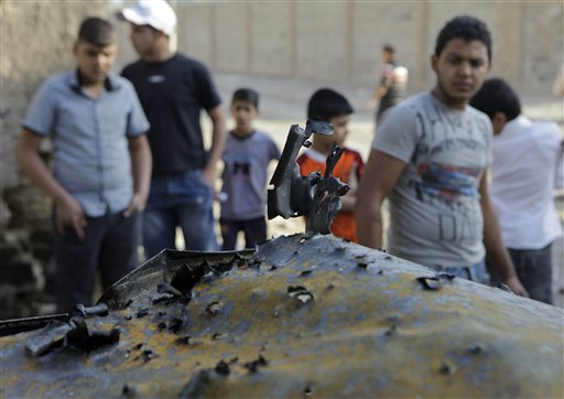 People inspect a destroyed car at the scene of a bomb attack in Baghdad, Iraq, Wednesday, Nov. 10, 2010. A string of bombings targeted Christian houses in Baghdad early Wednesday, killing and wounding several people, police said. (AP Photo/Khalid Mohammed)