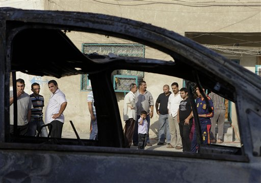 People inspect the scene of a bomb attack in Baghdad, Iraq, Wednesday, Nov. 10, 2010. A string of bombings targeted Christian houses in Baghdad early Wednesday, killing and wounding several people, police said. (AP Photo/Khalid Mohammed)