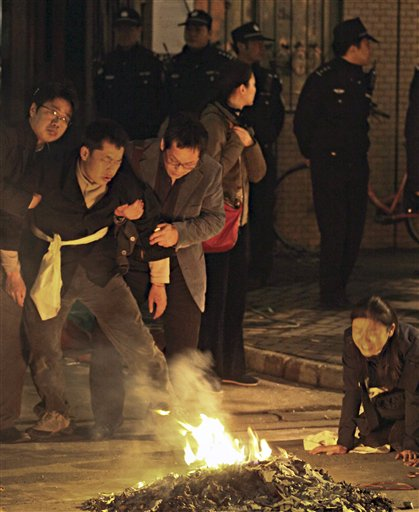 Chinese police officers stand watch the relatives mourn for victims who has killed in the Monday fire on an apartment building in Shanghai, China Tuesday Nov. 16, 2010. Police detained unlicensed welders Tuesday for accidentally starting a fire that engulfed the high-rise apartment building under renovation in China's business capital that killed at least 53 as public anger grew over the government's handling of the disaster. (AP Photo) ** CHINA OUT **
