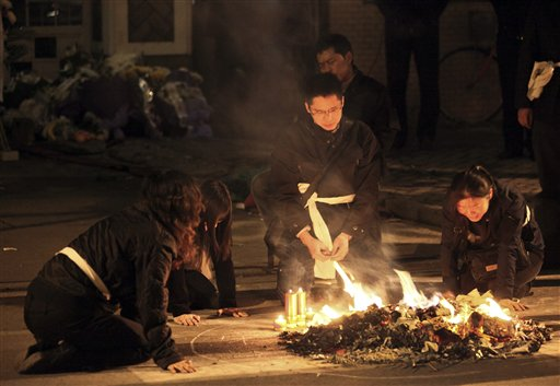 Relatives burn the belongings of their relatives who were killed in the Monday fire on an apartment building in Shanghai, China Tuesday Nov. 16, 2010. Police detained unlicensed welders Tuesday for accidentally starting a fire that engulfed the high-rise apartment building under renovation in China's business capital that killed at least 53 as public anger grew over the government's handling of the disaster. (AP Photo) ** CHINA OUT **