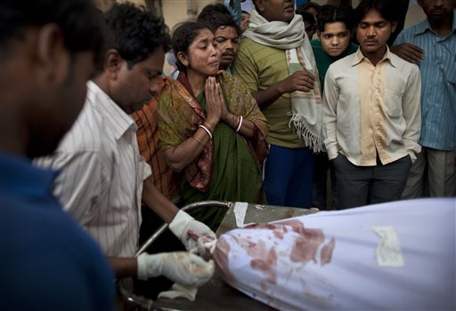 An Indian woman, center, reacts as the body of her husband who died in the collapse of a four-story apartment building is taken away for burial from a mortuary in New Delhi, India, Tuesday, Nov. 16, 2010. Dozens of residents were killed and scores injured when the 15-year-old building housing about 200 people collapsed late Monday night, police reports said. (AP Photo/Kevin Frayer)