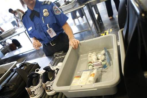 FILE - In this June 27, 2008 file photo, shoes and small liquid containers are placed in bins to be screened by TSA Supervisor Jennifer Haslip at the x-ray machine at Washington's Ronald Reagan National Airport. The TSA has demonstrated a knack for ignoring the basics of customer relations, while struggling with what experts say is an all but impossible task. It must stand as the last line against unknown terror, yet somehow do so without treating everyone from frequent business travelers to the family heading home to visit grandma as a potential terrorist. (AP Photo/Pablo Martinez Monsivais, File)