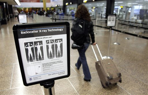 FILE - In this Nov. 19, 2010 file photo, a passenger walks past a sign informing travelers about the use of full-body scanners for TSA security screening at Seattle-Tacoma International Airport in Seattle. The TSA has demonstrated a knack for ignoring the basics of customer relations, while struggling with what experts say is an all but impossible task. It must stand as the last line against unknown terror, yet somehow do so without treating everyone from frequent business travelers to the family heading home to visit grandma as a potential terrorist. (AP Photo/Ted S. Warren, File)
