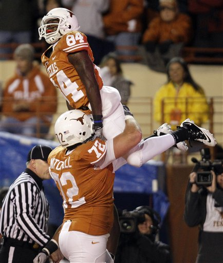 Texas' Marquise Goodwin (84) is hoisted in the air by teammate Britt Mitchell after scoring a touchdown against Texas A&M during the first quarter of an NCAA college football game, Thursday, Nov. 25, 2010, in Austin, Texas. (AP Photo/Eric Gay)