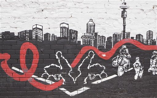 A wall mural in downtown Johannesburg Tuesday Nov. 23, 2010 shows a city skyline with an AIDS ribbon passing through workers who make a living in the town. The U.N. report says the global AIDS epidemic has slowed and cited a drop in new HIV infections with South Africa infection rate reduced by more than 25 percent in the past decade. (AP Photo/Denis Farrell)