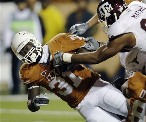 Texas' Cody Johnson (31) is brought down by Texas A&M's Jonathan Mathis, right, during the third quarter of an NCAA college football game, Thursday, Nov. 25, 2010, in Austin, Texas. (AP Photo/Eric Gay)