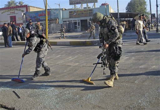 Iraqi security forces clean the street after a bomb attack in Baghdad, Iraq, Tuesday, Dec. 7, 2010. An early morning bomb attack targeted a police patrol in central Baghdad wounded several policemen and civilians, police said. (AP Photo/Khalid Mohammed)