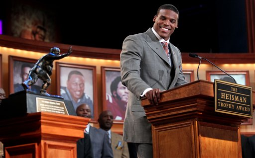 In this photo provided by the Heisman Trophy Trust, Auburn quarterback Cam Newton looks at the trophy while he makes his acceptance speech after being named the Heisman Trophy winner, Saturday, Dec. 11, 2010, in New York. (AP Photo/Heisman Trophy Trust, Kelly Kline) ** NO SALES **