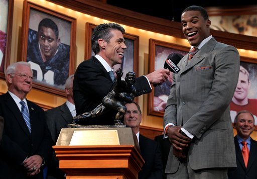In this photo provided by the Heisman Trophy Trust, Auburn quarterback Cam Newton, right, speaks with Chris Fowler, center, after being named the Heisman Trophy winner, Saturday, Dec. 11, 2010, in New York. (AP Photo/Heisman Trophy Trust, Kelly Kline) ** NO SALES **