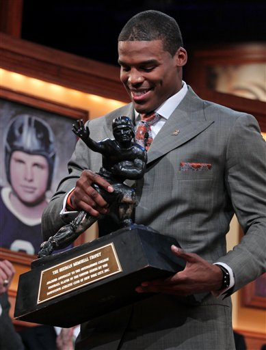 In this photo provided by the Heisman Trophy Trust, Auburn quarterback Cam Newton picks up the trophy after his acceptance speech following being named the Heisman Trophy winner, Saturday, Dec. 11, 2010, in New York. (AP Photo/Heisman Trophy Trust, Kelly Kline) ** NO SALES **