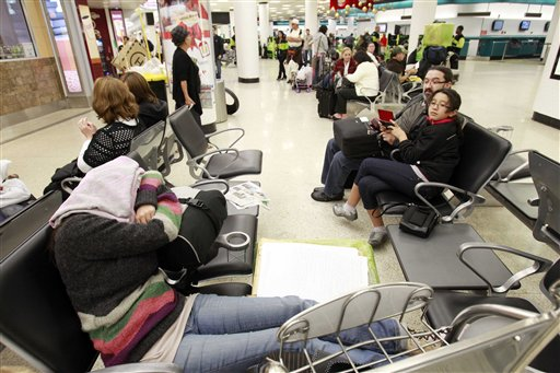 Candela Gonzalez, foreground, of Argentina, sleeps at Miami International Airport in Miami, Thursday, Dec. 23, 2010 as she waits for her flight to London where she will spend the holidays. (AP Photo/Alan Diaz)