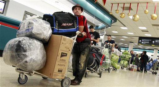 Travelers wait in line to check in as they prepare to travel to Cuba at Miami International Airport in Miami, Thursday, Dec. 23, 2010. (AP Photo/Alan Diaz)