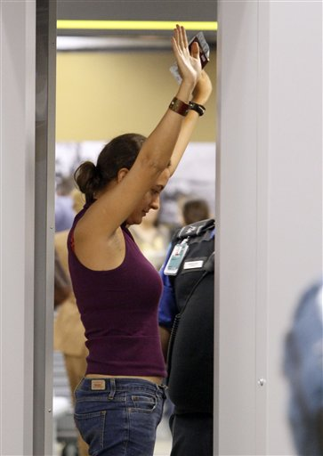 A passenger is scanned as she prepares to travel at Miami International Airport in Miami, Thursday, Dec. 23, 2010. (AP Photo/Alan Diaz)