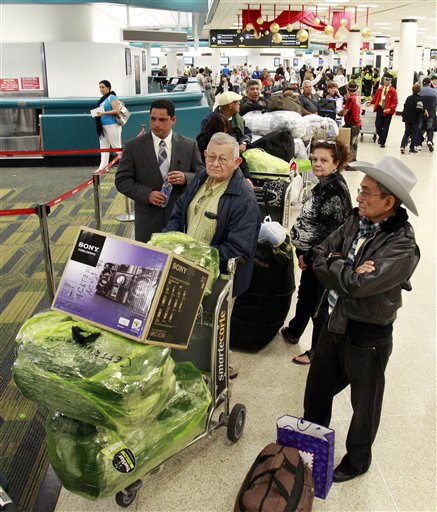 Passengers wait in line to check in as they prepare to travel to Cuba at Miami International Airport in Miami, Thursday, Dec. 23, 2010. (AP Photo/Alan Diaz)