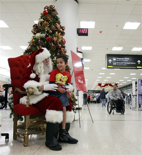 Mark Anthony Sepulveda, 6-years-old, of Hialeah, Fla., tells Santa his wishes for Christmas at Miami International Airport in Miami, Thursday, Dec. 23, 2010. (AP Photo/Alan Diaz)