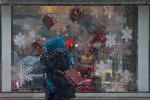 A woman covers her head with her scarf as she walks on the Michigan avenue in the snow in Chicago, Friday, Dec. 24, 2010. Light snow started falling this morning in Chicago and was expected to continue through the afternoon before tapering off this evening. (AP Photo/Nam Y. Huh)