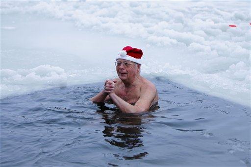 A member of the ice swimming club 'Seehunde Berlin' bathes in the frozen Oranke Lake in Berlin on Saturday, Dec. 25, 2010. Every Christmas the club arrange a Christmas swimming session in this lake. (AP Photo/Markus Schreiber)