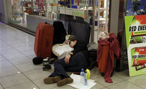 A man sleeps with his infant in a suitcase at Zaventem airport in Brussels on Friday, Dec. 24, 2010. A new batch of snow caused air traffic chaos in Belgium on Friday, with its main airport either canceling or delaying many flights. (AP Photo/Virginia Mayo)