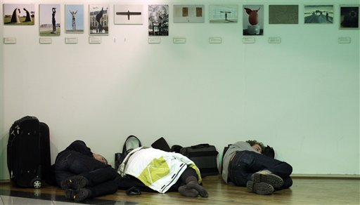 Three people sleep in a shop at Zaventem airport in Brussels on Friday, Dec. 24, 2010. A new batch of snow caused air traffic chaos in Belgium on Friday, with its main airport either canceling or delaying many flights. (AP Photo/Virginia Mayo)