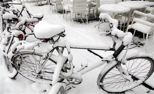 Snow covers bicycles and tables near the center of Antwerp, Belgium on Friday, Dec. 24, 2010. Belgium was blanketed with another batch of snow on Thursday evening adding to holiday travel chaos in the region. (AP Photo/Virginia Mayo)