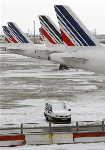 Planes are seen on the snow covered tarmac at the Charles-de-Gaulle Roissy airport, near Paris, Friday Dec. 24, 2010. The civil aviation authority asked Paris' Charles de Gaulle airport to cancel 20 percent of flights because of snow. (AP Photo/Jacques Brinon)