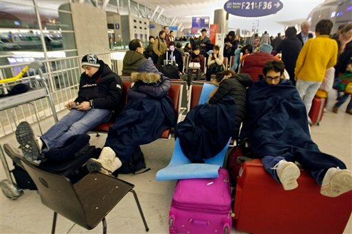 Passengers wait for their flights in a terminal after sleeping a night at the Charles-de-Gaulle Roissy airport, near Paris, Friday Dec. 24, 2010. The civil aviation authority asked Paris' Charles de Gaulle airport to cancel 20 percent of flights because of snow. (AP Photo/Jacques Brinon)