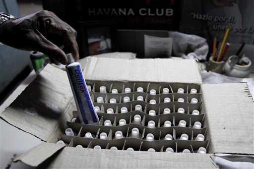 Worker Adrian Lopez shows a box of toothpaste at a government store in Havana, Cuba, Wednesday Dec. 29, 2010. Cuba's official Gazette reported Wednesday that effective Jan. 1, 'personal cleanliness products' are to be cut from the ration books that islanders have come to rely on for a small but steady supply of basic goods. The ration program began in 1962 as a temporary way to guarantee food staples for all Cubans in the face of the United States' then-new embargo. (AP Photo/Franklin Reyes)