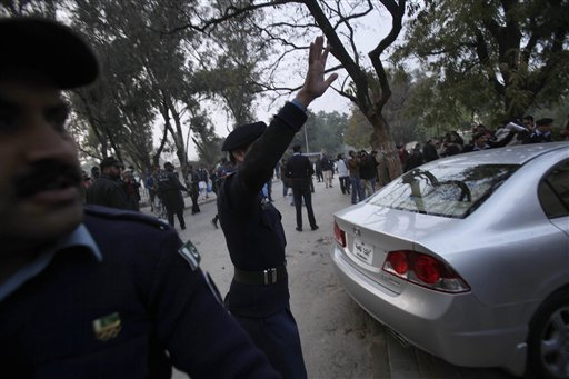 Pakistani police officers ask the crowd to leave the site where Punjab Gov. Salman Taseer was shot dead by one of his guards, in Islamabad, Pakistan, Tuesday, Jan. 4, 2011. The governor of Pakistan's powerful Punjab province was shot dead Tuesday by one of his guards in the Pakistani capital, police said, the killing was the most high-profile assassination of a political figure in Pakistan since the slaying of former Prime Minister Benazir Bhutto in December of 2007. (AP Photo/Muhammed Muheisen)