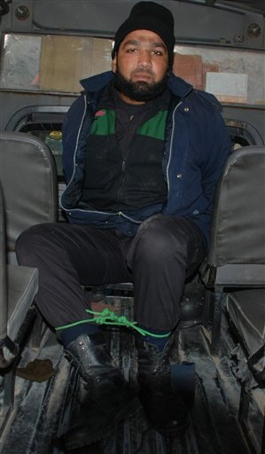 Commando of Pakistan's Elite force Mumtaz Qadri, who allegedly killed Punjab's governor Salman Taseer sits in a police vanin Islamabad, Pakistan on Tuesday, Jan. 4, 2011. An intelligence official interrogating the suspect, identified as Mumtaz Qadri, told The Associated Press that the bearded elite force police commando was boasting about the assassination, saying he was proud to have killed a blasphemer. The governor of Pakistan's powerful Punjab province was shot dead Tuesday by one of his guards in the Pakistani capital, police said, the killing was the most high-profile assassination of a political figure in Pakistan since the slaying of former Prime Minister Benazir Bhutto in December of 2007. (AP Photo/Irfan Ali)