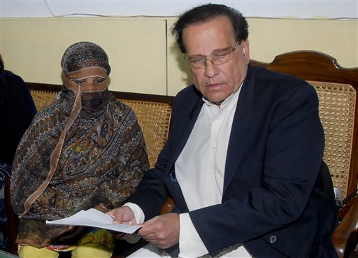 FILE - In this Nov. 20, 2010 file photo, Salman Taseer, right, Governor of Pakistani Punjab Province, listens to Pakistani Christian woman Asia Bibi, left, at a prison in Sheikhupura near Lahore, Pakistan. Taseer was shot dead Tuesday, Jan. 4, 2011, by one of his guards in the Pakistani capital, apparently because he had spoken out against the country's controversial blasphemy laws, officials said. The killing of Taseer was the most high-profile assassination of a political figure in Pakistan since the slaying of former Prime Minister Benazir Bhutto in December 2007, and it rattled a country already dealing with crises ranging from a potential collapse of the government to Islamist militancy. (AP Photo/File)