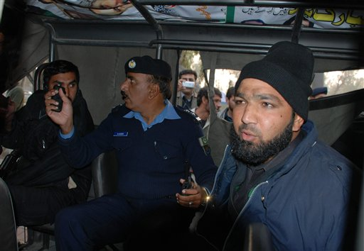 Commando of Pakistan's Elite force Mumtaz Qadri, right, who allegedly killed Punjab's governor Salman Taseer sits in a police custody in Islamabad, Pakistan on Tuesday, Jan. 4, 2011. An intelligence official interrogating the suspect, identified as Mumtaz Qadri, told The Associated Press that the bearded elite force police commando was boasting about the assassination, saying he was proud to have killed a blasphemer. The governor of Pakistan's powerful Punjab province was shot dead Tuesday by one of his guards in the Pakistani capital, police said, the killing was the most high-profile assassination of a political figure in Pakistan since the slaying of former Prime Minister Benazir Bhutto in December of 2007. (AP Photo/Irfan Ali)