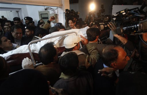 People carry dead body of Punjab's governor Salman Taseer who was shot dead by one of his guards, to an ambulance at a local hospital in Islamabad, Pakistan on Tuesday, Jan. 4, 2011. The governor of Pakistan's powerful Punjab province was shot dead Tuesday by one of his guards in the Pakistani capital, police said, the killing was the most high-profile assassination of a political figure in Pakistan since the slaying of former Prime Minister Benazir Bhutto in December of 2007. (AP Photo/B.K.Bangash)