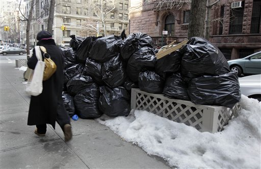 A woman walks by bags of uncollected trash on New York's Upper West Side, Thursday, Jan. 6, 2011. Another storm took aim at New York City, where Mayor Michael Bloomberg was still under fire for slow cleanup of a stubborn winter blast that kept streets clogged for days and delayed trash pickups, causing uncollected garbage to pile up for more than a week. (AP Photo/Richard Drew)
