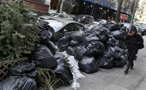 A woman walks by bags of uncollected trash and discarded Christmas trees on New York's Upper West Side, Thursday, Jan. 6, 2011. Another storm took aim at New York City, where Mayor Michael Bloomberg was still under fire for slow cleanup of a stubborn winter blast that kept streets clogged for days and delayed trash pickups, causing uncollected garbage to pile up for more than a week. (AP Photo/Richard Drew)