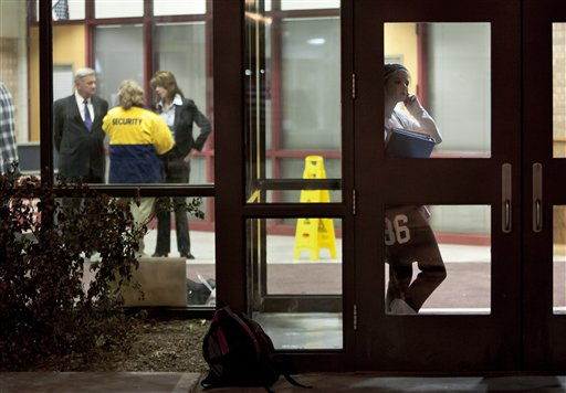 An unidentified student is framed by a door at Millard South high school in Omaha, Neb., Friday, Jan. 7, 2011. Classes resume Friday at the school where a 17-year-old shot two administrators, killing one, before fleeing and committing suicide. At left is Millard Superintendent Keith Lutz. (AP Photo/Nati Harnik)