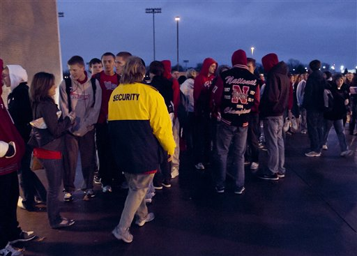 A woman wearing a security jacket walks past students as they gathered at the entrance to Millard South high school in Omaha, Neb., early morning Friday, Jan. 7, 2011, before classes resume for the first time since a 17-year-old student shot two administrators, killing one, before fleeing and committing suicide. (AP Photo/Nati Harnik)