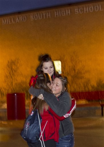 Students hug at Millard South high school in Omaha, Neb., early Friday, Jan. 7, 2011. Classes resume Friday after a 17-year-old student shot two administrators, killing one, before fleeing and committing suicide. (AP Photo/Nati Harnik)