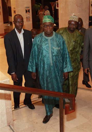 Former Nigerian President Olusegun Obasanjo, center, leaves his hotel for a meeting with incumbent Ivorian President Laurent Gbagbo, in Abidjan, Ivory Coast, Saturday, Jan. 8, 2011. Obasanjo made an unannounced visit to Ivory Coast late Saturday in an effort to help resolve the country's deepening political crisis after several other West African leaders have failed to persuade the incumbent to cede power.(AP Photo/Rebecca Blackwell)