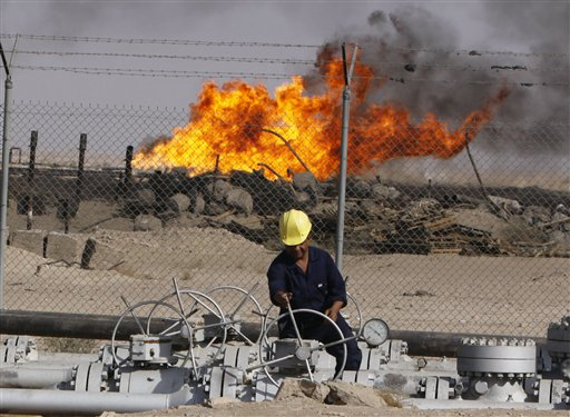 In this Dec. 13, 2009 file photo, an Iraqi worker operates valves at the Rumaila oil refinery, near the city of Basra, 550 kilometers (340 miles) southeast of Baghdad, Iraq. Iraq is hoping to rake in tens of billions of dollars from its oil sector. But it's not a matter of simply ramping up production from the fields _ it's how to deal with it once it starts flowing. Iraq's perennial security woes and a government still struggling to get its footing and direction all contribute to the uncertainty of how to these projects will move forward.(AP Photo/ Nabil al-Jurani, File)